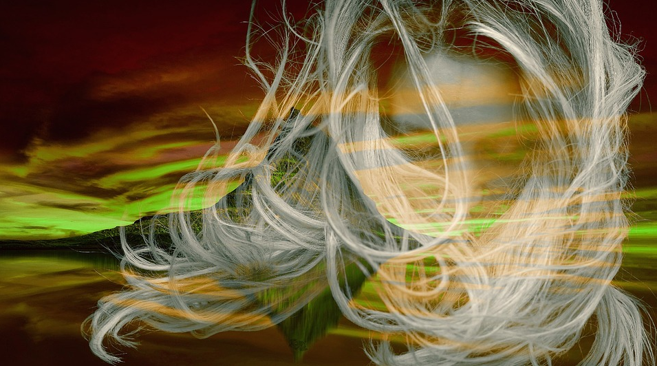 close up of blonde woman with long hair swirling around her face
