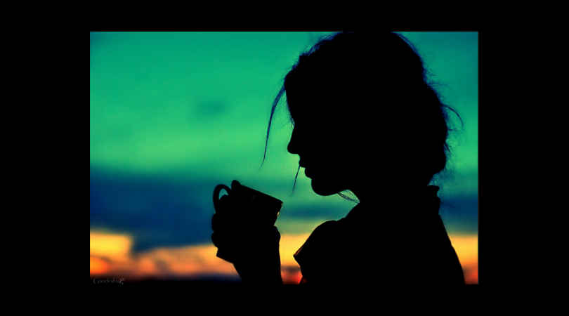 silouette of abused young woman holding coffee mug