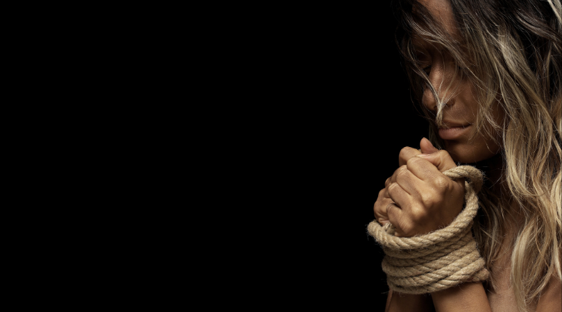 frightened, abused woman with hands tied